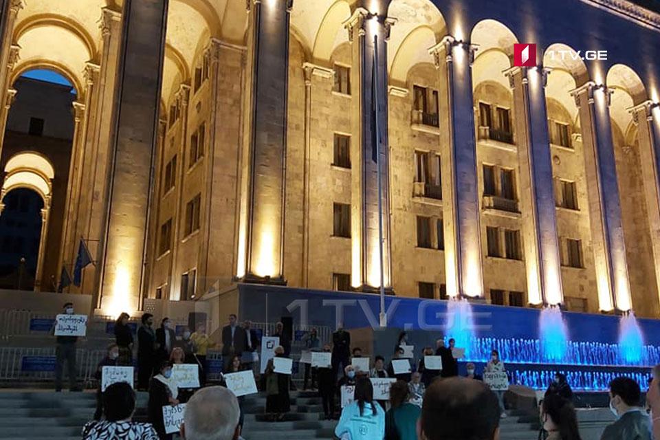 Члены движения «Затронь меня амнистией» проводят митинг перед зданием парламента