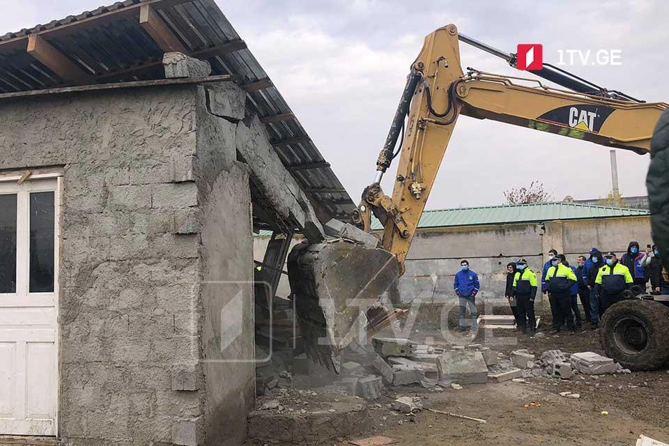 აფრიკის დასახლებაში, სადაც უკანონოდ აშენებული შენობების დემონტაჟი მიმდინარეობს, ხმაურია